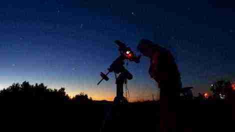 Astrónomo mirando a través de un telescopio